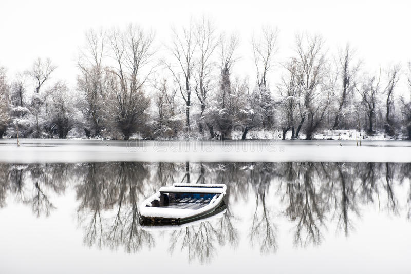 Zaniechana łódź w zamarzniętym jeziorze fotografia stock