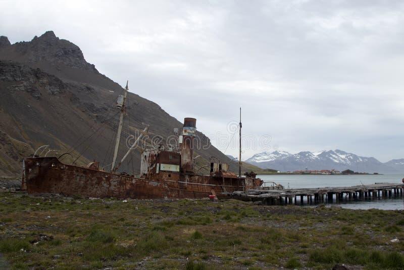 Zaniechana łódź wyrzucać na brzeg blisko porzuconego mola zdjęcia royalty free