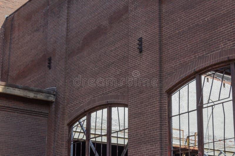 Zaniechana magazynowa ściana z cegieł z rdzewieć metal nadokienne ramy, żadny szkło obraz stock