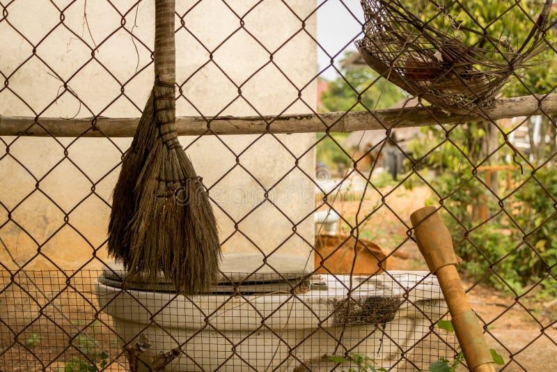 Zaniechana Stara miotła, kosz i PVC drymba na Ośniedziałym Drucianym ogrodzeniu z Brudną toaletą, obrazy stock