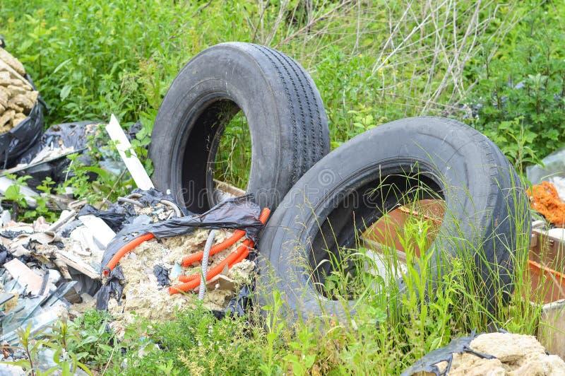 Zaniechane stare samochodowe opony w naturze ?mieciarski usyp w naturze kryzysu ekologiczny ?rodowiskowy fotografii zanieczyszcze obrazy royalty free