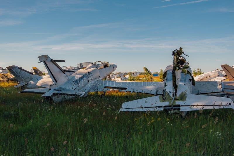 Zaniechani łamający starzy Radzieccy militarni myśliwscy samoloty na trawiastej ziemi zdjęcie stock