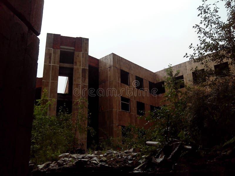 Zaniechany budynek przerastający z krzakami na dnie zdjęcia stock