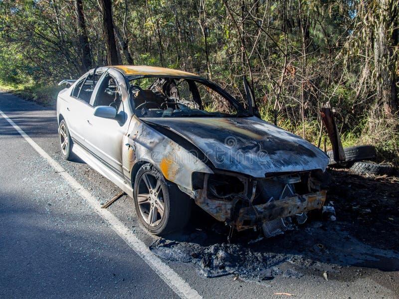 Zaniechany burnt out samochód przy drogowym strona przodu wizerunkiem obraz stock
