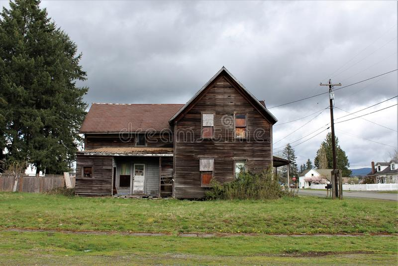 Zaniechany dom w granicie Spada, WA boczny widok z betonuje łuk w frontowym jardzie zdjęcia stock