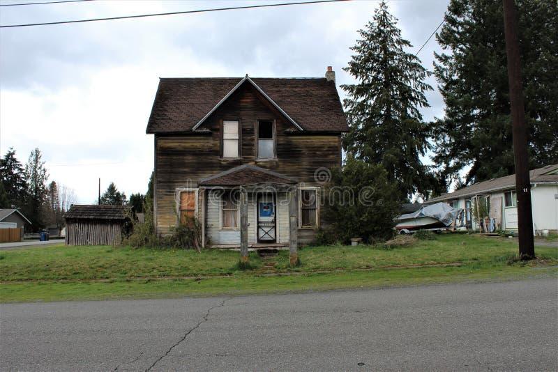 Zaniechany dom w Granitowych spadkach WA & x28; frontowy view& x29; z betonowym łukiem w frontowym jardzie zdjęcie stock