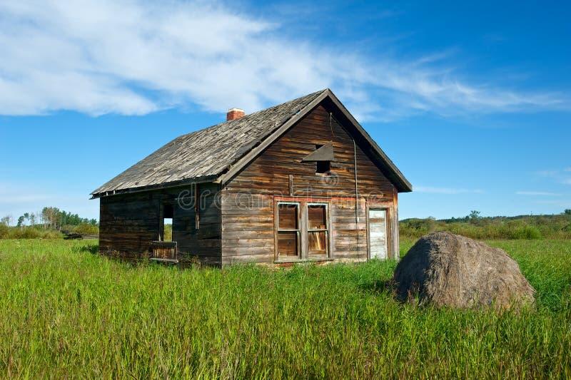 Zaniechany dom w trawiastym polu obrazy stock
