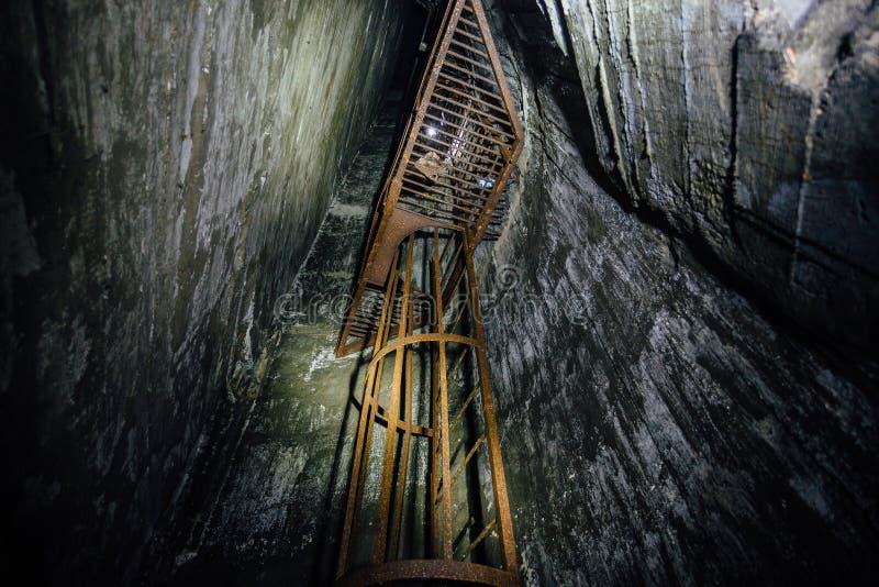 Zaniechany głęboki pionowo podziemny kopalniany dyszel Stara ośniedziała żelazna drabina zdjęcia stock