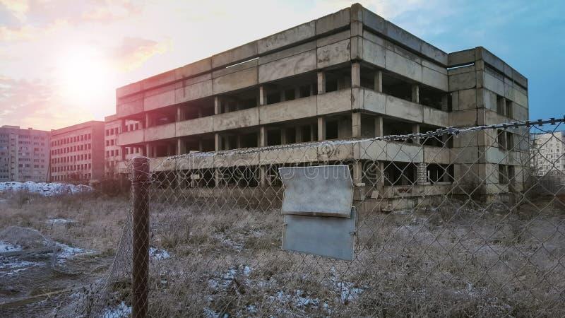 Zaniechany niedokończony budynek za ogrodzeniem w wieczór zdjęcia royalty free