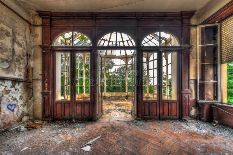 Zaniechany pokój z widokiem przez pięknego łamającego konserwatorium fotografia stock