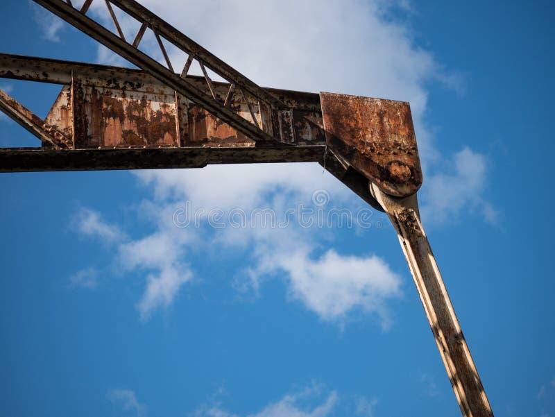 Zaniechany, rdzewiejący, przemysłowy podnośny żuraw, winch w disused doku/ zdjęcie stock