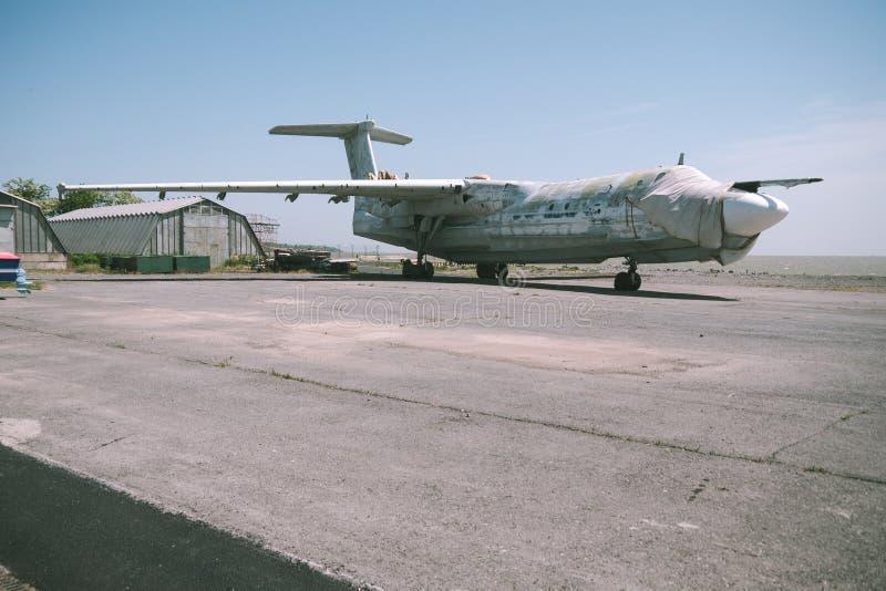 Zaniechany samolot wojskowy na pustym lotnisku blisko hangaru przeciw niebieskiemu niebu zdjęcia stock