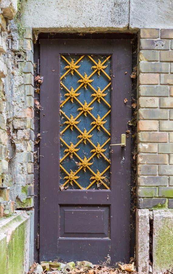 Zaniechany stary drzwi z żółtym metalem na ściana z cegieł fotografia royalty free