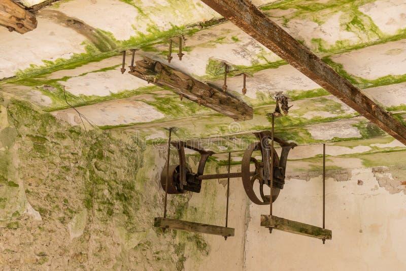 Zaniechany wodny młyn Ośniedziali koła i zielony mech zakrywali starą ścianę z cegieł fotografia royalty free