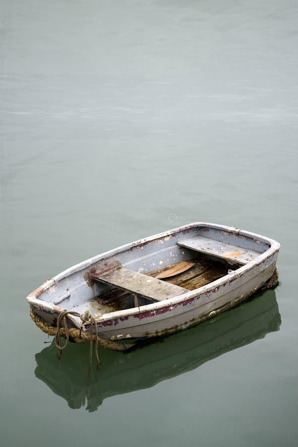 Zaniedbana stara wioślarska łódź na spokojnej wodzie morskiej zdjęcie royalty free