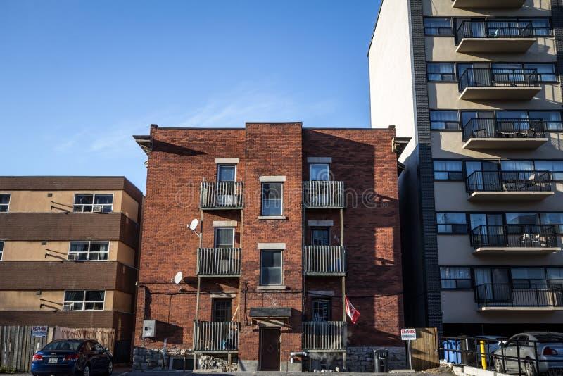 Zaniedbany ma?y budynek mieszkaniowy w mieszkaniowej ulicie w Ottawa, Ontario, podczas jesieni popo?udnia z samochodami parkuj?cy fotografia stock
