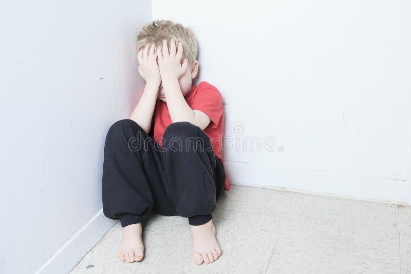 Zaniedbany osamotniony dziecko opiera przy ścianą fotografia royalty free