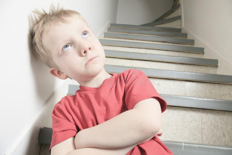 Zaniedbany osamotniony dziecko opiera przy ścianą obraz royalty free