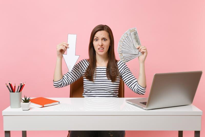 Zaniepokojona kobieta trzyma puszek wartości spadku strzałę, plika dolary udziały, gotówkowa pieniądze praca przy białym biurkiem obrazy stock
