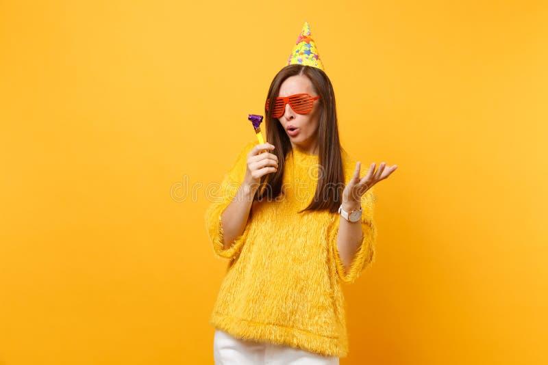 Zaniepokojona kobieta w pomarańczowych śmiesznych szkłach, urodzinowy kapeluszowy patrzeć na bawić się fajczane podesłanie ręki,  obraz stock