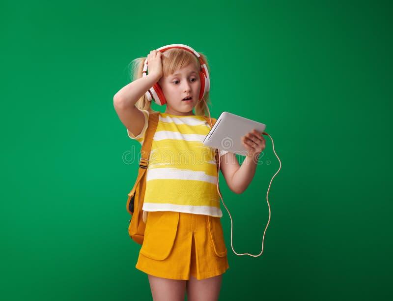 Zaniepokojona szkolna dziewczyna patrzeje pastylka peceta w he?mofonach obrazy stock