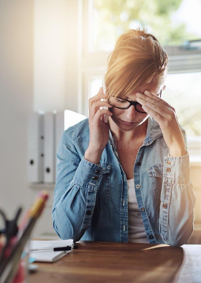 Zaniepokojony żeński przedsiębiorca opowiada na telefonie fotografia royalty free