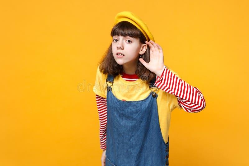 Zaniepokojony dziewczyna nastolatek w francuskich bereta i drelichu sundress podsłuchuje z przesłuchanie gestem odizolowywającym  zdjęcia royalty free
