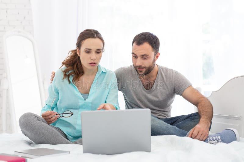 Zaniepokojony kobieta w ciąży i mężczyzna zagłębianie w wideo zdjęcie royalty free