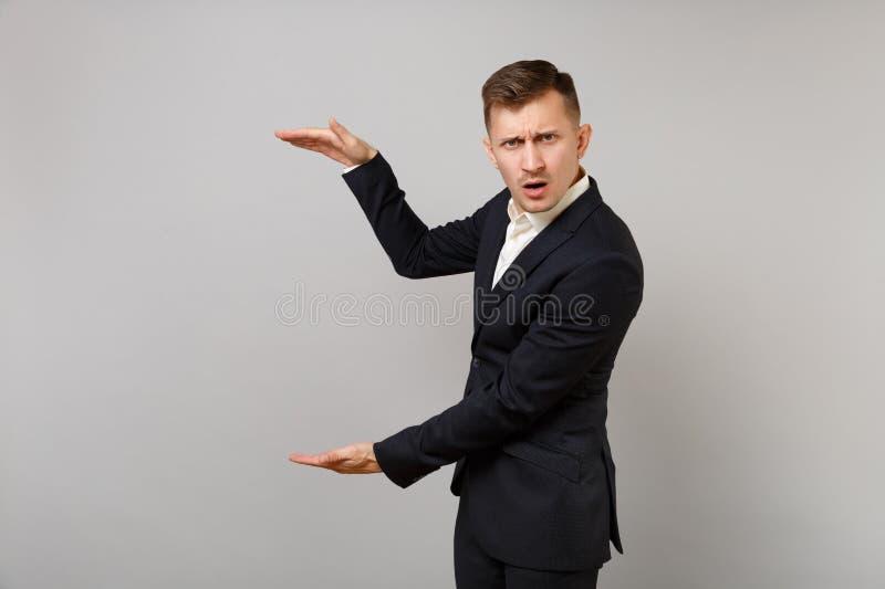 Zaniepokojony młody biznesowy mężczyzna gestykuluje w klasycznym czarnym kostiumu demonstrujący rozmiar z pionowo kopii przestrze obraz royalty free
