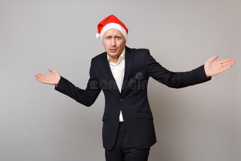 Zaniepokojony młody biznesowy mężczyzna w klasycznego czarnego kostiumu podesłania Bożenarodzeniowych kapeluszowych rękach odizol obrazy stock