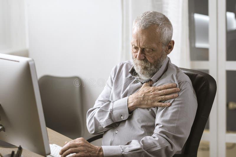 Zaniepokojony starszy mężczyzna ma atak serca zdjęcia royalty free