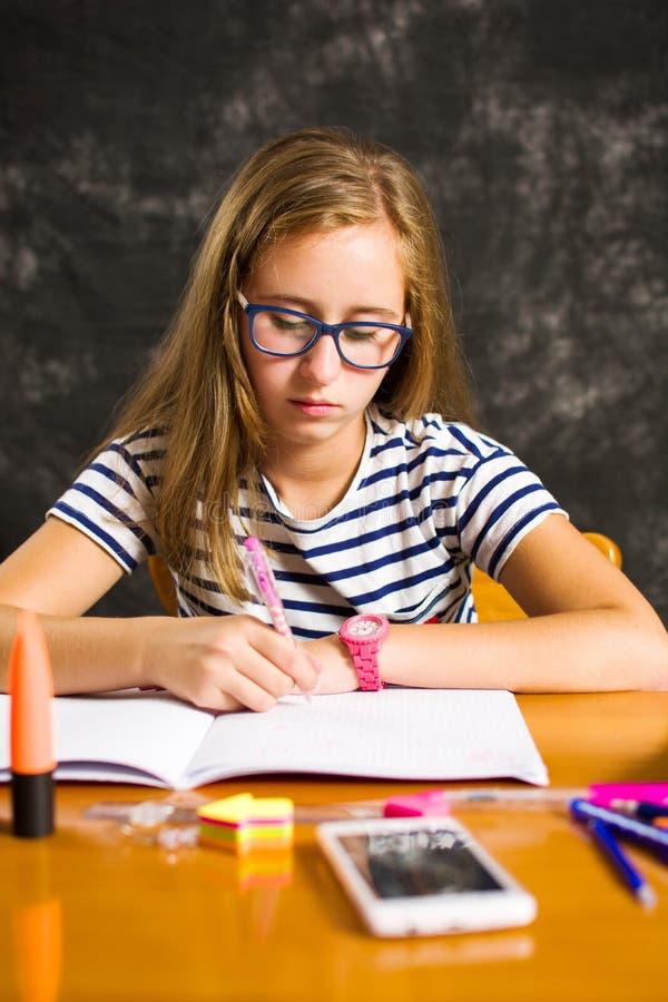 Zanudzająca dziewczyna robi pracie domowej w domu obraz royalty free
