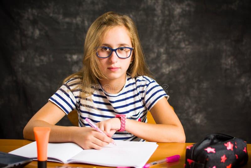 Zanudzająca dziewczyna robi pracie domowej w domu fotografia royalty free