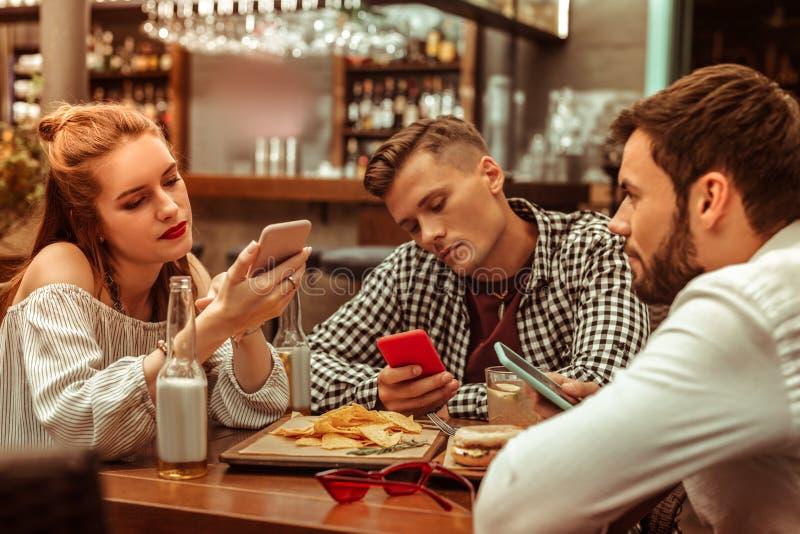 Zanudzająca grupa trzy przyjaciela klei ich telefony obrazy royalty free