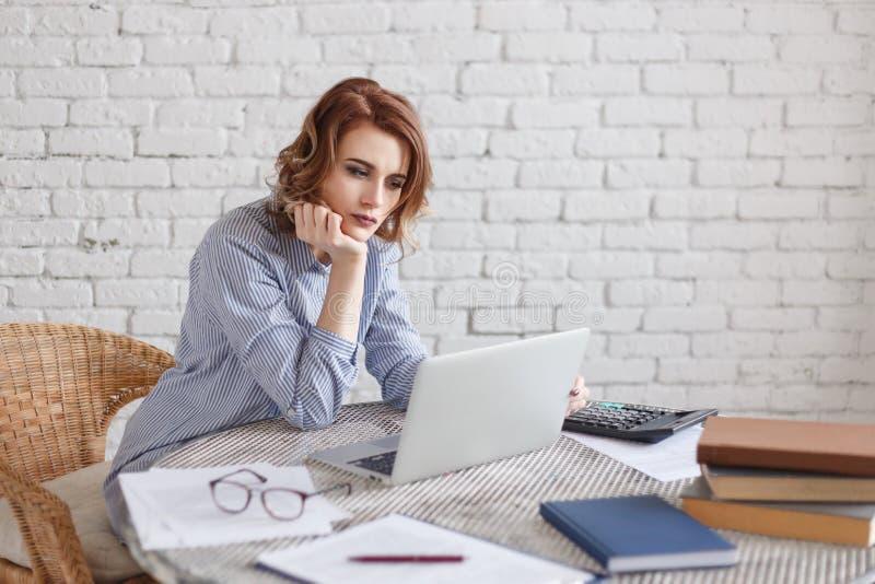 Zanudzająca młoda kobieta w biurowym działaniu z laptopem i gapić się przy ekranem komputerowym obraz royalty free