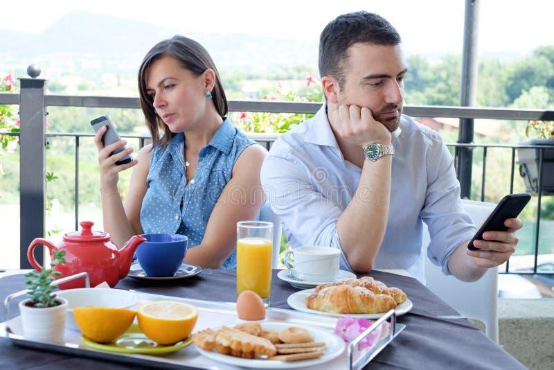 Zanudzająca para używa mądrze telefon podczas śniadaniowego czasu zdjęcia royalty free