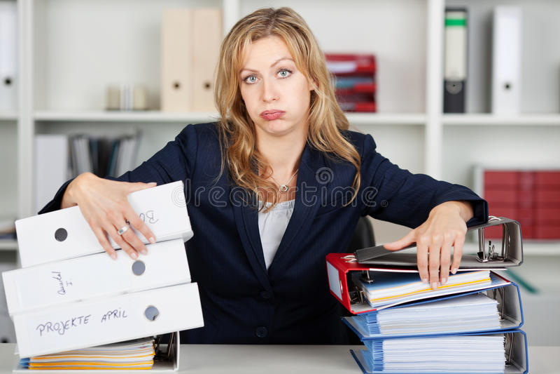 Zanudzający bizneswoman Za Brogującymi segregatorami Przy biurkiem fotografia stock