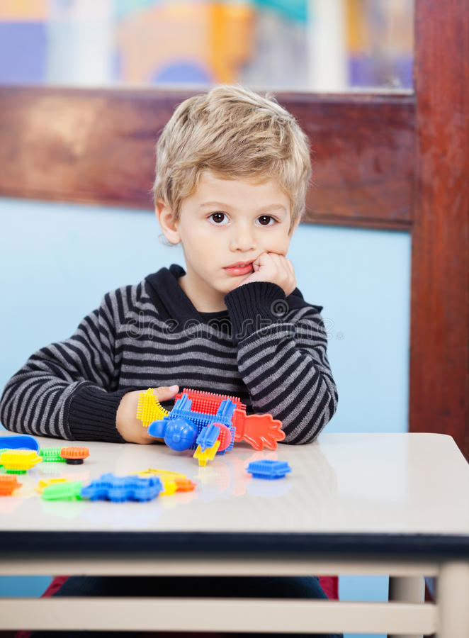 Zanudzający chłopiec mienie Blokuje obsiadanie Przy biurkiem Wewnątrz fotografia royalty free
