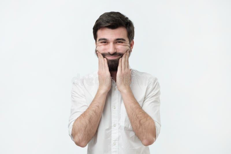 Zanudzający latynoski mężczyzna z brody mienia ręką na policzku, przyglądający chory i zmęczony obraz stock