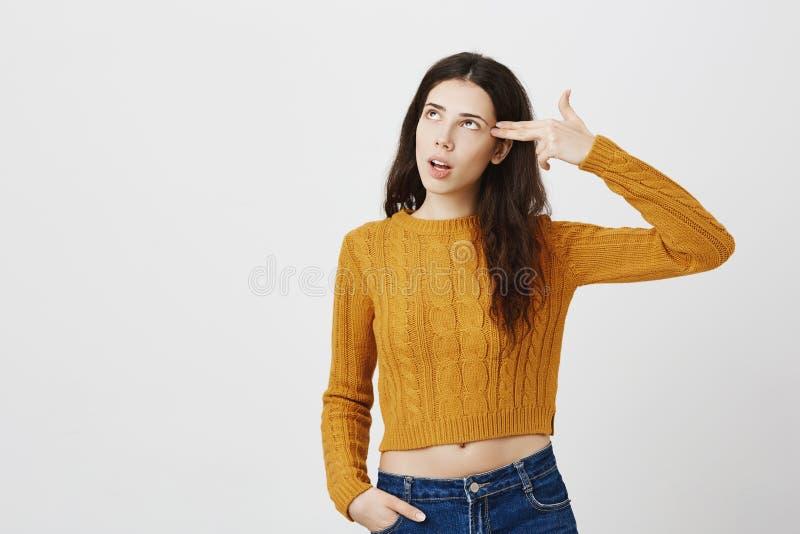 Zanudzający lub dokuczający europejski dziewczyna seansu pistoletu gest blisko świątyni, przyglądającej up podczas gdy mówić bla  zdjęcia royalty free