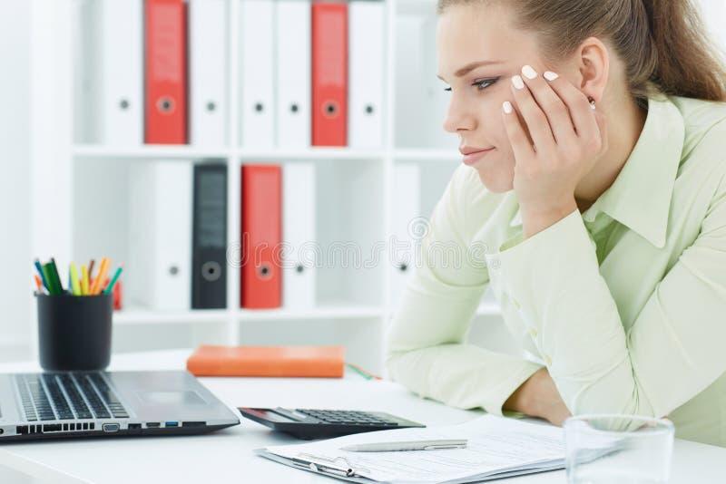 Zanudzający młody żeński urzędnik siedzi przy jej spojrzeniami przy ekranem komputerowym i biurkiem zdjęcia royalty free