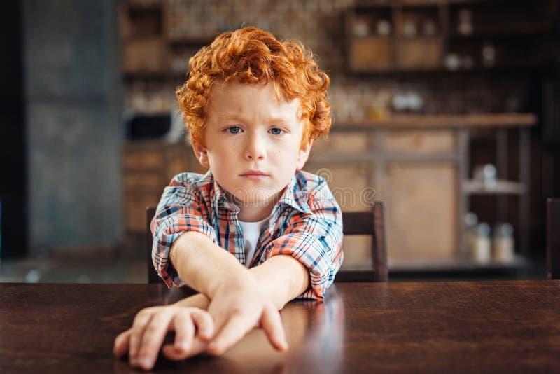 Zanudzający rudzielec chłopiec obsiadanie przy stołem obraz royalty free
