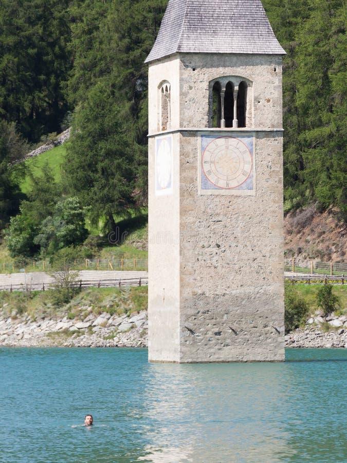Zanurzający wierza reschensee kościół, mężczyzna dopłynięcie obok go zdjęcie royalty free