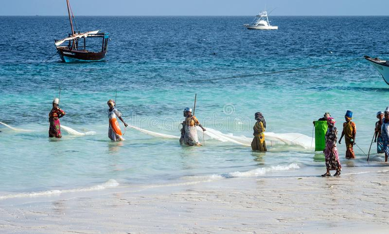 Zanzibar, Τανζανία, Ανατολική Αφρική - 23 Ιουνίου 2017: Οι αφρικανικές γυναίκες από ένα ψαροχώρι πιάνουν τα μικρά ψάρια από την α στοκ φωτογραφία με δικαίωμα ελεύθερης χρήσης