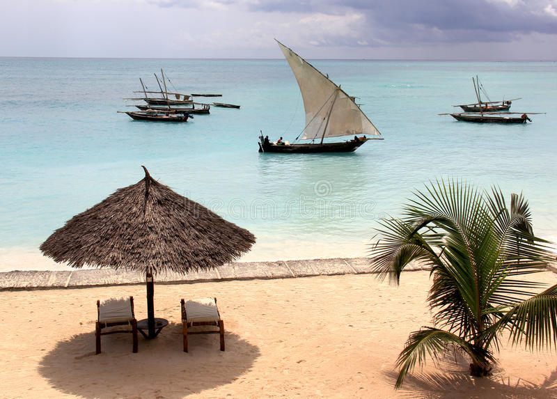 Zanzibar Beach. A dhow sails past an idyllic beach in Nungwi, Zanzibar royalty free stock photo