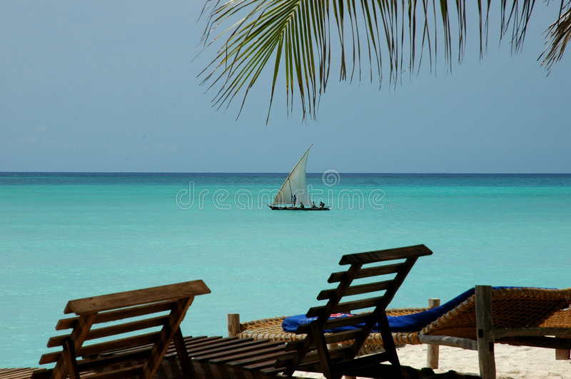 Zanzibar Blue. Dhow framed by Palm tree in the North of Zanzibar royalty free stock photos