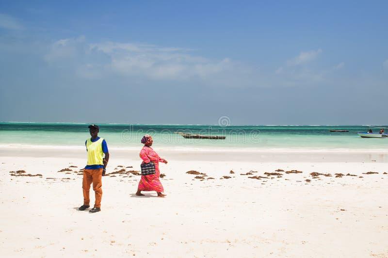 Zanzibar people on the beach. Kiwengwa, Zanzibar - 15 January, 2015: local people walking on a warm winter day on the beach near Indian ocean on Zanzibar, sailor royalty free stock photos