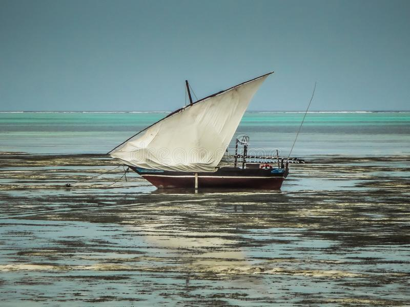 Zanzibar beach during low tide with a wooden fishing boat royalty free stock photo