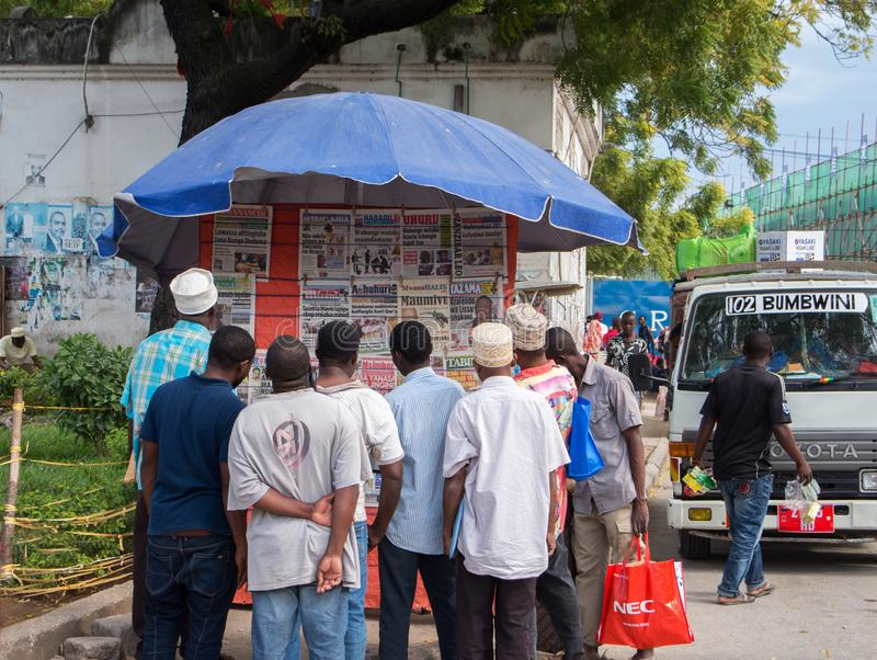 Local residents read newspapers on a stand in the city center stock photos