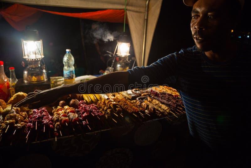 Zanzibari-Straßenhändler und Chef und Imbisse am Nachtstraßen-Nahrungsmittelmarkt in Forodhani-Gärten Steinstadt, Sansibar-Stadt, stockbilder